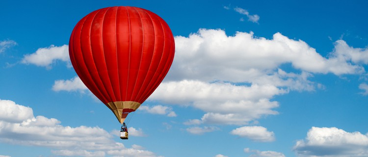 red hot air balloon in cloudy sky