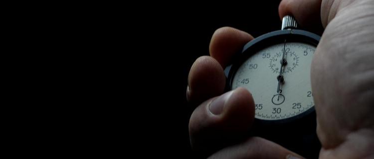 hand holding analogue stopwatch