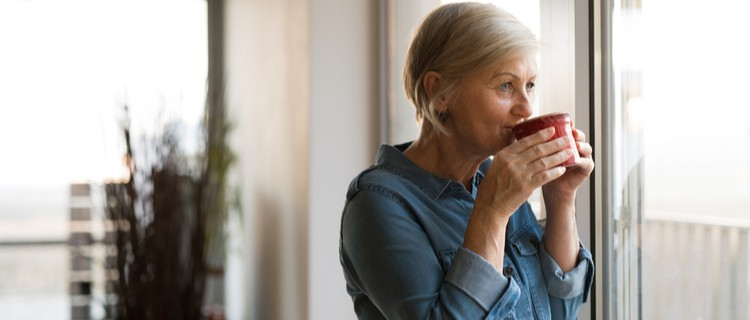 older woman looking out of her window with a hot drink